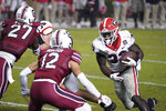 Georgia running back Daijun Edwards (33) carries the ball against South Carolina defensive back Joey Hunter (12) during the second half of an NCAA college football game Saturday, Nov. 28, 2020, in Columbia, S.C. (AP Photo/Sean Rayford)