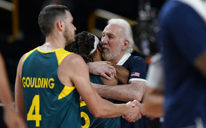United States's head coach Gregg Popovich, right, hugs Australia's Patty Mills (5) at the end of men's basketball semifinal game between the United States and Australia at the 2020 Summer Olympics, Thursday, Aug. 5, 2021, in Saitama, Japan. (AP Photo/Eric Gay)