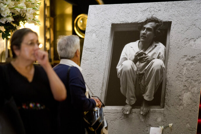 People walk up to a photo and works by the late Mexican painter Francisco Toledo, displayed during a memorial at the Bellas Artes Palace in Mexico City, Friday, Sept. 6, 2019. Toledo, who was well-known and respected in Mexico both for his art and his activism, has died, the country's president announced late Thursday. (AP Photo/Eduardo Verdugo)