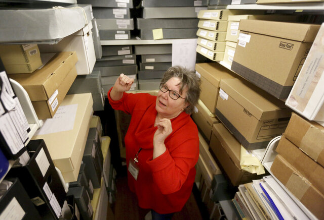 In this Friday, March 27, 2020 photo, Mary Lovell Swetnam, the special collections librarian at Virginia Beach, Va.  Central Library, looks for the 1858 sale of deed detailing the sale of four slaves in then Princess Anne County in the library's archives. (Stephen M. Katz/The Virginian-Pilot via AP)