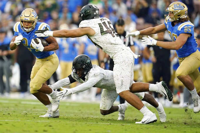 UCLA running back Zach Charbonnet, left, runs against Oregon during the second half of an NCAA college football game Saturday, Oct. 23, 2021, in Pasadena, Calif. (AP Photo/Marcio Jose Sanchez)