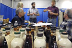 In this Monday, Jan. 29, 2018 photo, a panel judges maple syrup entries at the annual Vermont Farm Show in Essex Junction, Vt. Each year a panel of judges rates the entries in the state that is the largest producer of maple syrup. (AP Photo/Lisa Rathke)