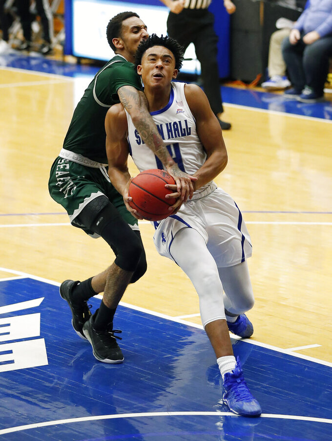 Seton Hall guard Jared Rhoden (14) is fouled by Wagner guard Alex Morales (2) on his way to the basket during the second half of an NCAA college basketball game Tuesday, Nov. 5, 2019, in South Orange, N.J. (AP Photo/Noah K. Murray)