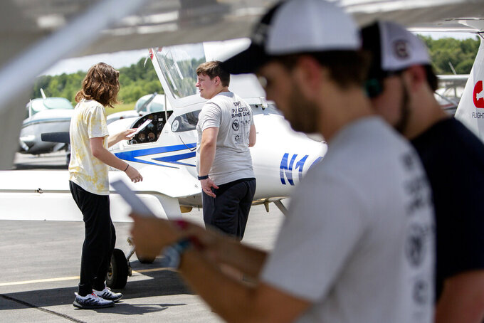 Aiden Saer, left, listens to certified flight instructor Chris Olds, center, go over the pre-flight checklist for the Diamond DA20 at the Summerville Airport Wednesday, July 14, 2021, in Dorchester County, S.C. Seven high school students and recent grads are participating in CRAFT's first-ever summer camp from July 11 to 23 at the Summerville Airport. The goal of the camp is to give high schoolers a head start on receiving a pilot's license, said Jay Aldea, co-owner of CRAFT. (Gavin McIntyre/The Post And Courier via AP)