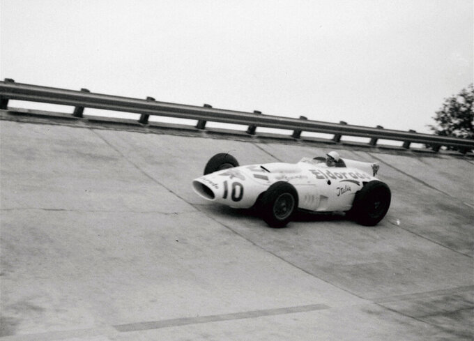 FILE - In this file photo dated  June 24, 1958, British racing driver Stirling Moss takes a curve on the Monza circuit in Italy, in the new Maserati Eldorado Special which he will drive in the forthcoming Monza 500.  Stirling Moss has died at the age of 90, according to an announcement Sunday April 12, 2020, from his family.(AP Photo, FILE)