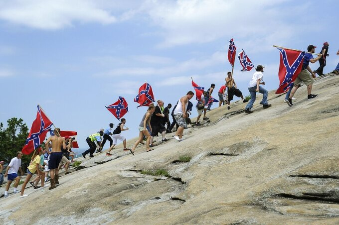 FILE - In this Aug. 1, 2015, file photo, Confederate flag supporters climb Stone Mountain to protest what they believe is an attack on their Southern heritage during a rally at Stone Mountain Park in Stone Mountain, Ga.  The Stone Mountain Memorial Association has denied a gathering permit from the Sons of Confederate Veterans, who were looking to host their annual Confederate Memorial Day service at Stone Mountain Park outside Atlanta.  The gathering was slated for Saturday, April 17, 2021,  but a March 31 letter from memorial association CEO Bill Stephens denied the necessary permit, The Atlanta Journal-Constitution reported.  (AP Photo/John Amis, File)