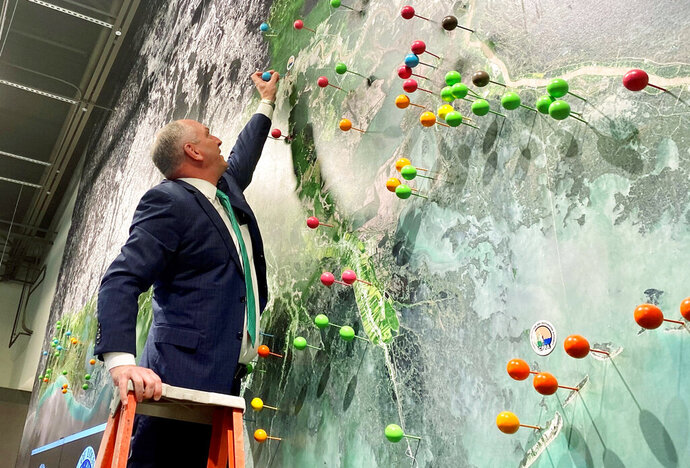 In this photo provided by the Coastal Protection and Restoration Authority, Louisiana Gov. John Bel Edwards sticking a large pin in a mural of Louisiana's coast, in Baton Rouge, La., Wednesday, Feb. 12, 2020, to show the location of the Maurepas Swamp. A council created to allocate money from water pollution fines paid after the catastrophic BP oil spill voted Wednesday to give Louisiana $130 million to link the state's second-largest coastal swamp back up to the Mississippi River, providing fresh water and sediment to nourish it. (Coastal Protection and Restoration Authority via AP)