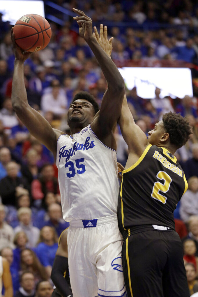 Kansas center Udoka Azubuike (35) shoots while defended by Milwaukee forward Harrison Henderson (2) during the first half of an NCAA college basketball game in Lawrence, Kan., Tuesday, Dec. 10, 2019. (AP Photo/Orlin Wagner)