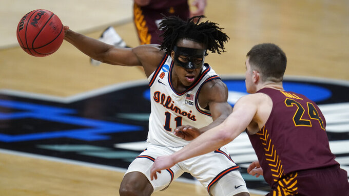 Illinois guard Ayo Dosunmu (11) drives on Loyola Chicago guard Tate Hall (24) during the first half of a men's college basketball game in the second round of the NCAA tournament at Bankers Life Fieldhouse in Indianapolis, Sunday, March 21, 2021. (AP Photo/Paul Sancya)