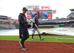 New York Yankees starting pitcher Masahiro Tanaka, center, and his translator, Shingo Horie, left, walk off the field at Nationals Park after it was announced that both of today's interleague baseball games against the Washington Nationals have been postponed due to inclement weather, Wednesday, May 16, 2018, in Washington. Both game have been rescheduled for June 18, 2018. (AP Photo/Pablo Martinez Monsivais)