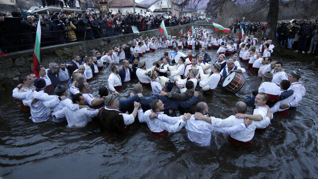 Citizens of the mountain town of Kalofer, in central Bulgaria, clad in traditional dresses stand in the icy Tundzha River, some waving national flags to recover a crucifix cast by a priest in an old ritual marking the feast of Epiphany, Wednesday, Jan. 6, 2021. The legend goes that the person who retrieves the wooden cross will be freed from evil spirits and will be healthy throughout the year. (AP Photo/Valentina Petrova)