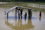 Rohingya refugees repair a shelter damaged following heavy rains at the Rohingya refugee camp in Kutupalong, Bangladesh, Wednesday, July 28, 2021. Days of heavy rains have brought thousands of shelters in various Rohingya refugee camps in Southern Bangladesh under water, rendering thousands of refugees homeless. (AP Photo/ Shafiqur Rahman)