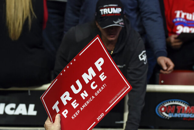 FILE - In this March 2, 2020, file photo a campaign worker hands out signs before President Donald Trump speaks during a campaign rally in Charlotte, N.C. Seven nights a week, Trump's reelection team is airing live programming online. The shows replace his trademark rallies, which have been impossible for now by the coronavirus pandemic. Trump himself has not yet appeared in his campaign's shows. (AP Photo/Mike McCarn, File)