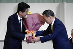 CORRECTS TO THAT JAPAN'S PRIME MINISTER SHINZO ABE RECEIVES FLOWER - Japan's Prime Minister Shinzo Abe, left, receives flowers from Chief Cabinet Secretary Yoshihide Suga after Suga was elected as new head of Japan's ruling party at the Liberal Democratic Party's (LDP) leadership election Monday, Sept. 14, 2020, in Tokyo. The ruling LDP chooses its new leader in an internal vote to pick a successor to Prime Minister Shinzo Abe, who announced his intention to resign last month due to illness. (AP Photo/Eugene Hoshiko, Pool)