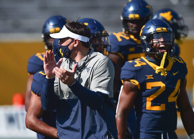 West Virginia head coach Neal Brown works with his team during warmups before an NCAA college football game against Baylor on Saturday, Oct. 3, 2020, in Morgantown, W. Va.  (William Wotring/The Dominion-Post via AP)
