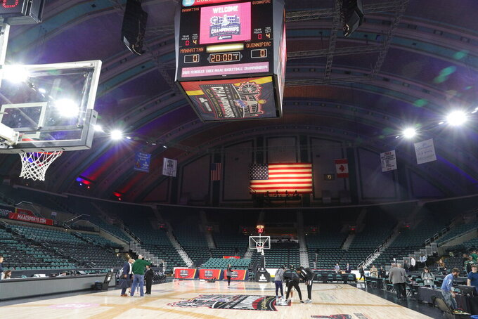 Staff and media mill about after the men's and women's NCAA college basketball games at the Metro Atlantic Athletic Conference tournament were canceled, Thursday March 12, 2020, due to coronavirus concerns. (Edward Lea Staff/The Press of Atlantic City via AP)