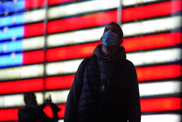 A man stops to watch election returns on electronic billboards in Times Square, Tuesday, Nov. 3, 2020, in New York. (AP Photo/Seth Wenig)