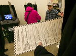 In this Nov. 4, 2014 file photo, a voter carries her ballot to be scanned at a polling place in New York's Chinatown neighborhood. A ballot measure will give New York City residents a chance to institute ranked choice voting in primaries and special elections. Under the system now in effect in cities such as San Francisco and Cambridge, Massachusetts as well as the entire state of Maine, voters can rank candidates in order of preference instead of choosing just one. (AP Photo/Richard Drew, File)