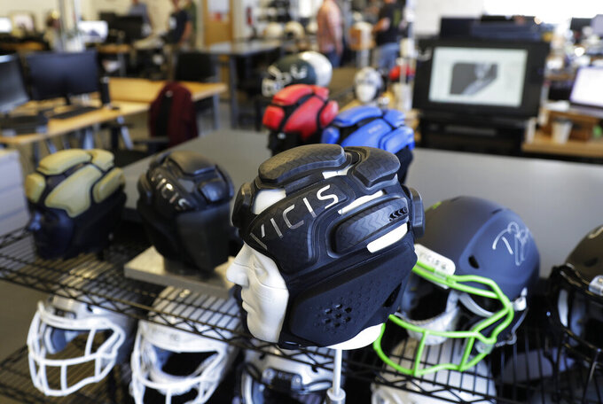 This photo taken May 23, 2019, shows helmets on a rack at the Seattle headquarters of football helmet maker VICIS. The company's latest offering is the ULTIM cap, which is intended for use with youth flag football and competitive 7-on-7 football played during the offseason for youth and high school programs. (AP Photo/Ted S. Warren)