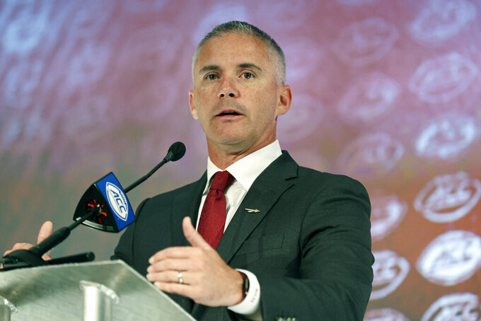 FILE - In this Thursday, July 22, 2021 file photo, Florida State head coach Mike Norvell speaks during an NCAA college football news conference at the Atlantic Coast Conference media days in Charlotte, N.C. Florida State is banking on improvement production from the Seminoles after spending the last nine months patching up holes at quarterback, on the offensive line, in the secondary and along the defensive line. Coach Mike Norvell he believes that production and leadership will come from a group of nine newcomers who transferred and are part of the Seminoles' two-deep depth chart. (AP Photo/Nell Redmond, File)