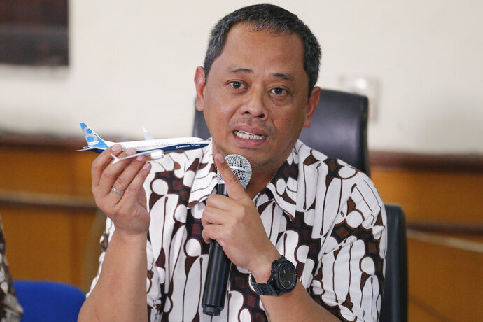 National Transportation Safety Committee investigator Nurcahyo Utomo holds a model of an airplane during a press conference in Jakarta, Indonesia, Friday, Oct. 25, 2019. An Indonesian investigation found a Lion Air flight that crashed and killed 189 people a year ago was doomed by a combination of aircraft design flaws, inadequate training and maintenance problems. (AP Photo/Tatan Syuflana)