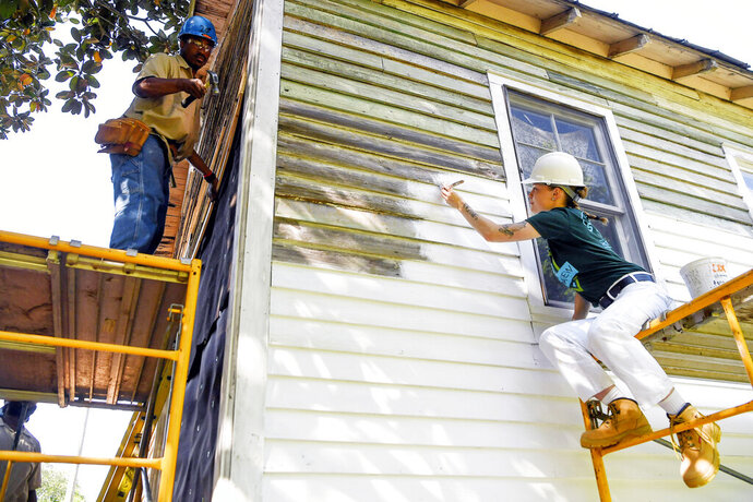 In this Thursday, May 2, 2019 photo, Smith Tucker, left, and Madisen Jones work on restoring the birthplace of Nina Simone in Tryon, N.C. The nearly 90-year-old home where Simone grew up in Tryon, north of the city's downtown, is being stabilized after years of neglect that nearly saw the structure be demolished. Workers from the National Trust for Historic Preservation's HOPE Crew plan to spend much of May replacing and painting exterior siding on the 660-square-foot structure ahead of additional work on windows, interior and the roof. (Angela Wihelm/The Asheville Citizen-Times via AP)