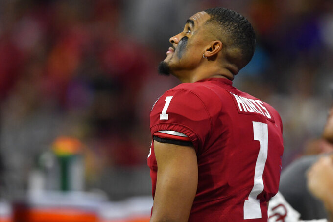 Oklahoma quarterback Jalen Hurts (1) watches a replay against LSU during the second half of the Peach Bowl NCAA semifinal college football playoff game, Saturday, Dec. 28, 2019, in Atlanta. (AP Photo/John Amis)