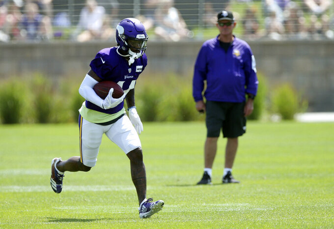 Minnesota Vikings wide receiver Stefon Diggs, left, runs a pass play as head coach Mike Zimmer watches during the NFL football team's training camp Monday, July 29, 2019, in Eagan, Minn. (AP Photo/Jim Mone)