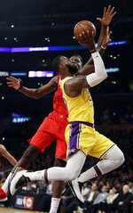 Los Angeles Lakers' LeBron James, front, drives to the basket as Houston Rockets' Clint Capela defends during the first half of an NBA basketball game Thursday, Feb. 21, 2019, in Los Angeles. (AP Photo/Marcio Jose Sanchez)