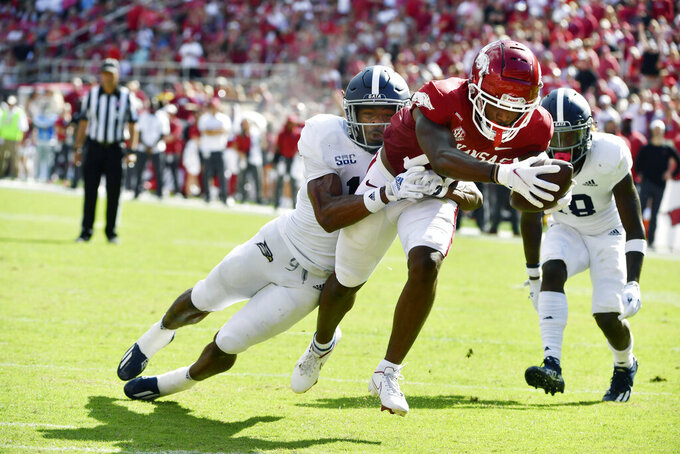 Georgia Southern corner back Darrell Baker Jr. (14) tries to tackle Arkansas receiver Tyson Morris (19) as he scores a touchdown during the first half of an NCAA college football game Saturday, Sept. 18, 2021, in Fayetteville, Ark. (AP Photo/Michael Woods)