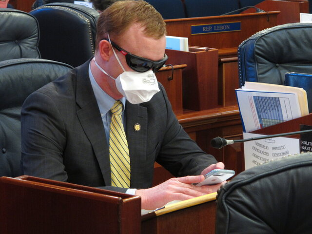 Alaska state Rep. David Eastman sits at his desk on the House floor on Monday, March 23, 2020, in Juneau, Alaska. Eastman, a Wasilla Republican, has been critical of the Legislature's planning around the coronavirus. Rep. Sharon Jackson also wore a mask on the House floor Monday. (AP Photo/Becky Bohrer)