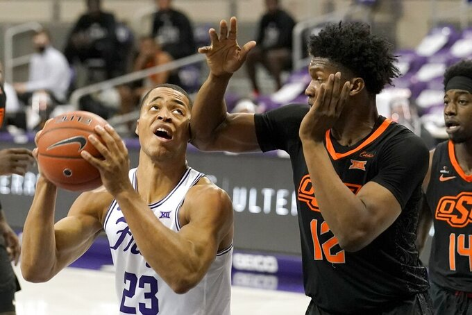TCU forward Jaedon LeDee (23) takes a shot to the face from Oklahoma State's Matthew-Alexander Moncrieffe (12) during the second half of an NCAA college basketball game in Fort Worth, Texas, Wednesday, Feb. 3, 2021. (AP Photo/Tony Gutierrez)