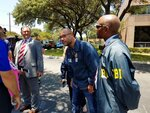 FBI agents examine the scenes Tuesday, August 13, 2019 where someone fired shots at two buildings in San Antonio that house officers connected to U.S. Immigration and Customs Enforcement. (Guillermo Contreras/The San Antonio Express-News via AP)