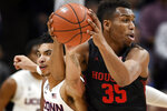 Connecticut's James Bouknight, left, reaches in and pressures Houston's Fabian White Jr., right, in the first half of an NCAA college basketball game, Thursday, March 5, 2020, in Storrs, Conn. (AP Photo/Jessica Hill)