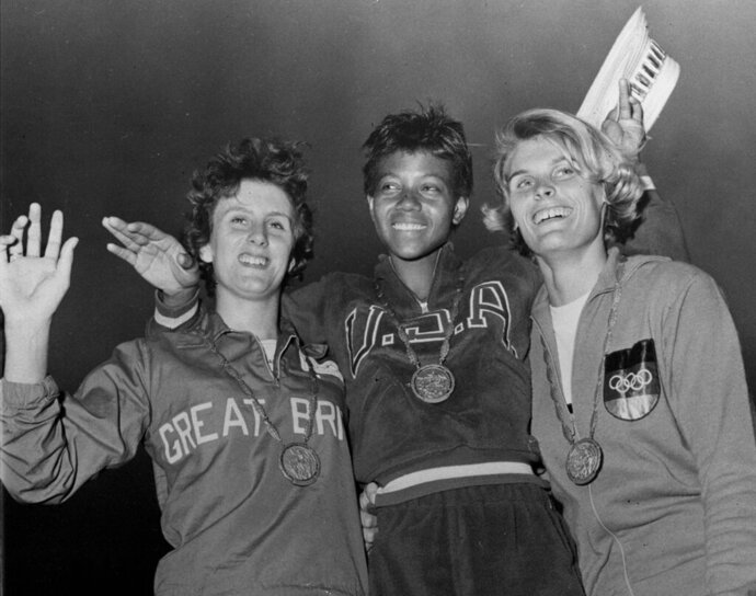 FILE - In this Sept. 5, 1960, file photo, the medalists in the women's 200-meter event, from left, bronze medalist Dorothy Hyman, of Great Britain; gold medalist Wilma Rudolph, of the United States, and silver medalist Jutta Heine, of Germany, pose with their medals at the Olympic stadium in Rome, Italy. The 1960 Rome Summer Olympics set the standard for every Olympiad to follow. These Games were the first televised in the United States, even if film of events had to be flown from Rome to New York where Jim McKay did the voice-overs the next day. (AP Photo/File)