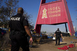 FILE - In this Dec. 19, 2017, file photo, two police officers, Eric Meier, right, and Curtis Bynum from the Anaheim Police Department's homeless outreach team walk through a homeless encampment set up outside Angel Stadium to hand out flyers about the community outreach day in Anaheim, Calif. Homeless residents and their advocates are expected to argue in U.S. court Tuesday, Feb. 13, that Orange County can't remove them from a riverbed bike trail without adequate housing options. Officials say they've offered shelter beds and housing. (AP Photo/Jae C. Hong, File)