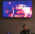 FILE- In this Aug. 16, 2018, file photo, Balch Springs police officer Tyler Gross watches Roy Oliver's body cam footage during the trial of fired Balch Springs police officer Roy Oliver, who is charged with the murder of 15-year-old Jordan Edwards, at the Frank Crowley Courts Building in Dallas. The body camera footage played a key role in Oliver's conviction. (Rose Baca/The Dallas Morning News via AP, Pool)