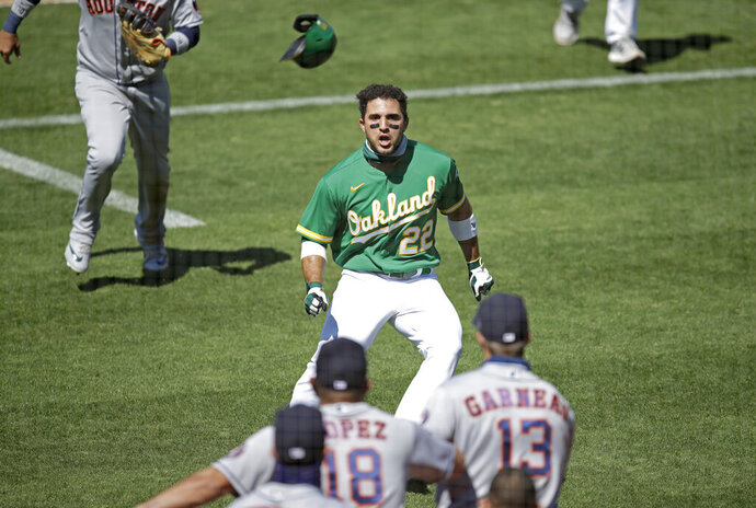 Oakland Athletics' Ramon Laureano (22) charges the Houston Astros dugout after being hit by a pitch thrown by Humberto Castellanos in the seventh inning of a baseball game Sunday, Aug. 9, 2020, in Oakland, Calif. (AP Photo/Ben Margot)
