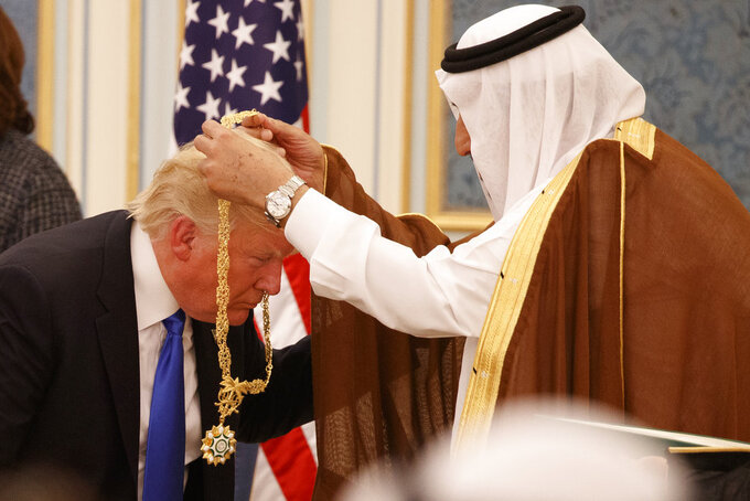 FILE -- In this May 20, 2017 file photo, Saudi King Salman presents President Donald Trump with the highest civilian honor, the Collar of Abdulaziz Al Saud, at the Royal Court Palace, in Riyadh, Saudi Arabia. Crown Prince Mohammed bin Salman's first trip abroad since the killing of Saudi journalist Jamal Khashoggi will offer an early indication of whether he will face any repercussions. The prince will attend the Group of 20 Summit in Argentina, where he will come face to face with Trump, who appears keen to preserve their friendship, as well as European leaders and Turkey's president, who has stepped up pressure on the kingdom. (AP Photo/Evan Vucci, File)