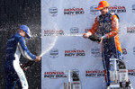 Scott Dixon, left, sprays teammate and second-place finisher Felix Rosenqvist after winning an IndyCar Series auto race, Sunday, July 28, 2019, at Mid-Ohio Sports Car Course in Lexington, Ohio. (AP Photo/Tom E. Puskar)