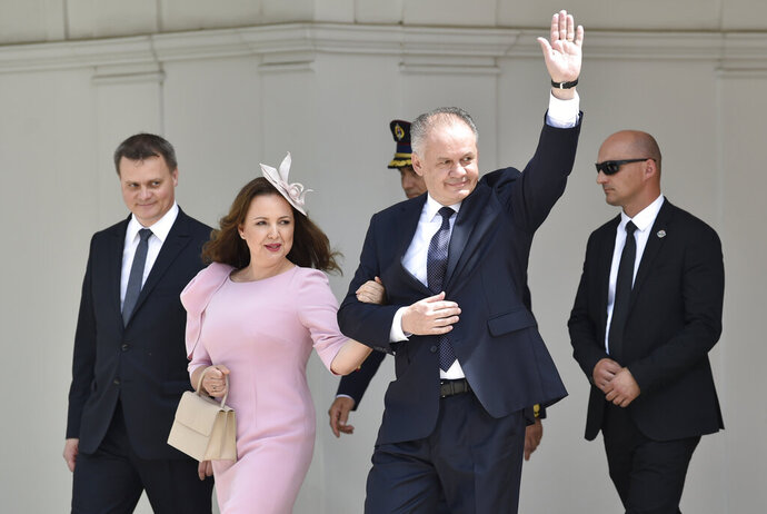 Outgoing Slovak President Andrej Kiska accompanied by his wife Martina waves farewell in front of the Presidential Palace in Bratislava before new Slovak President Zuzana Caputova takes her presidential oath in Bratislava, Slovakia, Saturday, June 15, 2019. (Dalibor Gluck/CTK via AP)
