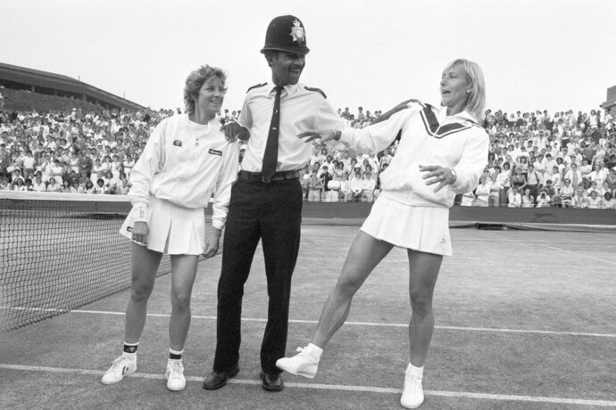 FILE - In this July 4, 1985, file photo, Chris Evert, left, and Martina Navratilova joke with Police Constable Les Bowie on Number Two Court at Wimbledon, England. Navratilova successfully defended her title against Evert on July 6, 1985. (AP Photo/Dave Caulkin, File)