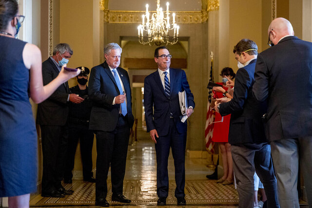 Treasury Secretary Steven Mnuchin, right, accompanied by White House chief of staff Mark Meadows, left, take a question from a reporter following a meeting with Senate Majority Leader Mitch McConnell of Ky. as negotiations continue on a coronavirus relief package on Capitol Hill in Washington, Tuesday, Aug. 4, 2020. (AP Photo/Andrew Harnik)