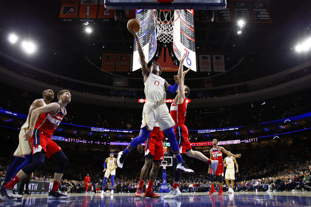 Philadelphia 76ers' Josh Richardson (0) shoots against Washington Wizards' Garrison Mathews (24) during the first half of an NBA basketball game, Saturday, Dec. 21, 2019, in Philadelphia. (AP Photo/Matt Slocum)