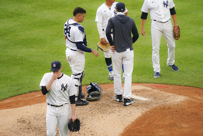 New York Yankees starting pitcher Jordan Montgomery, left, is relieved in the sixth inning of the first baseball game of a doubleheader against the New York Mets, Friday, Aug. 28, 2020, in New York. (AP Photo/John Minchillo)