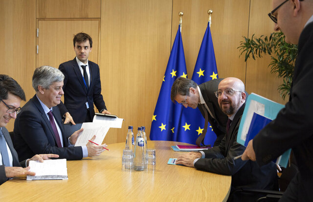 Eurogroup President and Portugal's Finance Minister Mario Centeno, second left, meets with European Council President Charles Michel, second right, at the Europa building in Brussels, Tuesday, Feb. 18, 2020. (AP Photo/Virginia Mayo, Pool)