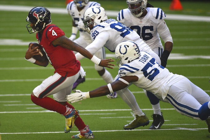 Houston Texans quarterback Deshaun Watson (4) is chased by Indianapolis Colts defensive end Kemoko Turay (57) and defensive tackle DeForest Buckner (99) during the first half of an NFL football game Sunday, Dec. 6, 2020, in Houston. (AP Photo/Eric Christian Smith)