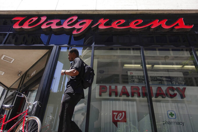 FILE - In this June 25, 2019, file photo a man walks outside a Walgreens pharmacy in downtown Cincinnati. Walgreens is adding the former leader of rival drugstore chain Rite Aid to its executive team. The company said Monday, Aug. 31, 2020, that John Standley will join Walgreens Boots Alliance as president, effective immediately.(AP Photo/John Minchillo, File)
