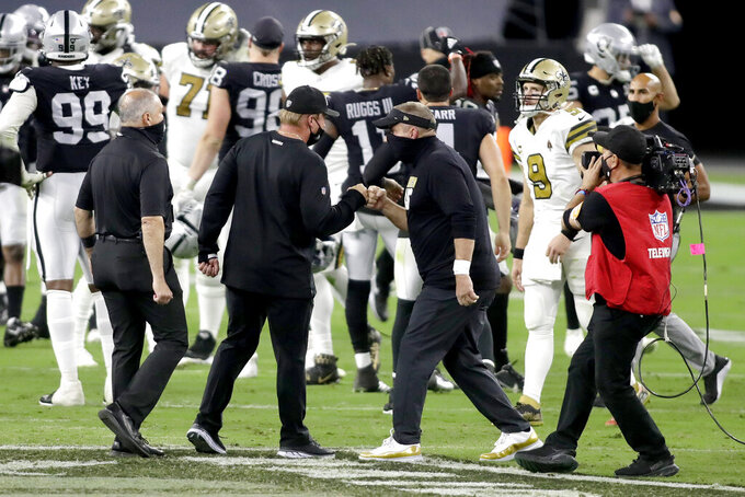 Las Vegas Raiders head coach Jon Gruden, left, bumps fists with New Orleans Saints head coach Sean Payton after an NFL football game, Monday, Sept. 21, 2020, in Las Vegas. (AP Photo/Isaac Brekken)