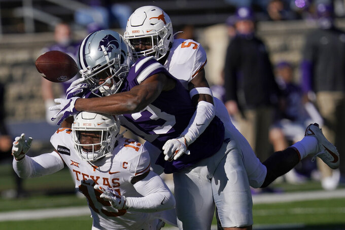 Texas defensive backs D'Shawn Jamison (5) and Chris Brown (15) break up a pass intended for Kansas State wide receiver Chabastin Taylor (13) during the first half of an NCAA college football game in Manhattan, Kan., Saturday, Dec. 5, 2020. (AP Photo/Orlin Wagner)